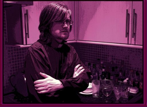 A man sits at a table with his arms crossed. The picture is tinted red.